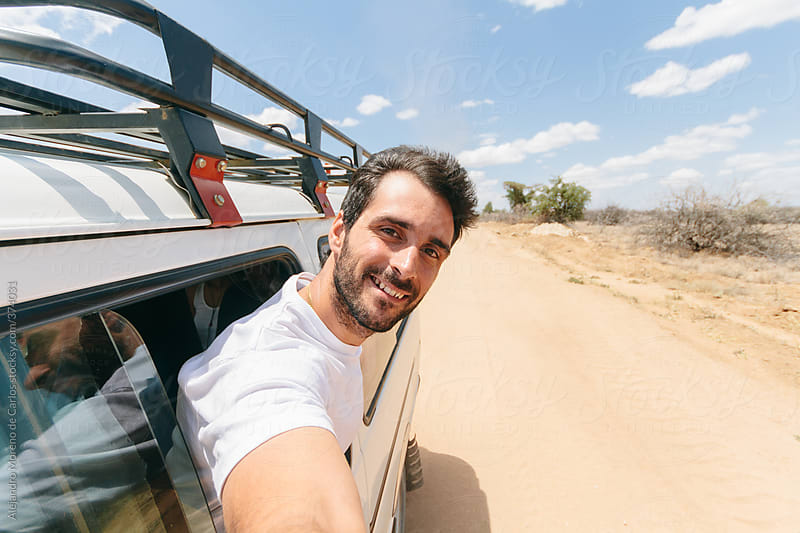 Young Man Selfie Out Of The Window Of A SUV Car On A Dirt Road On