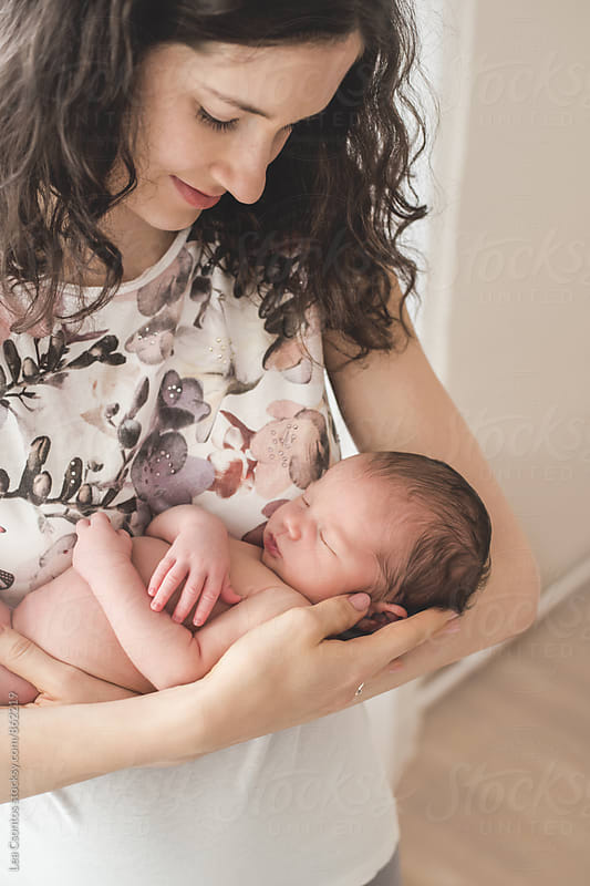 Beautiful mother holding her sleeping newborn baby and looking at him by Lea Csontos for Stocksy United