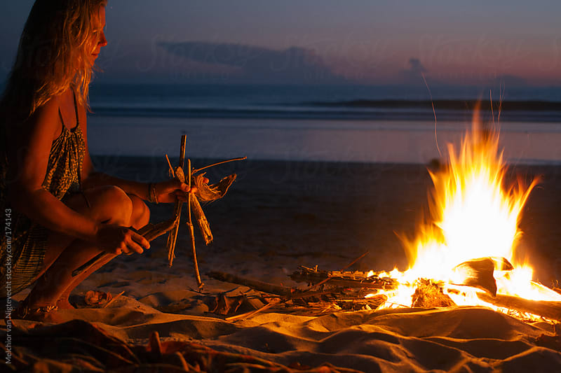 Girl makes a fire of driftwood on the beach with sunset by Melchior van Nigtevecht for Stocksy United