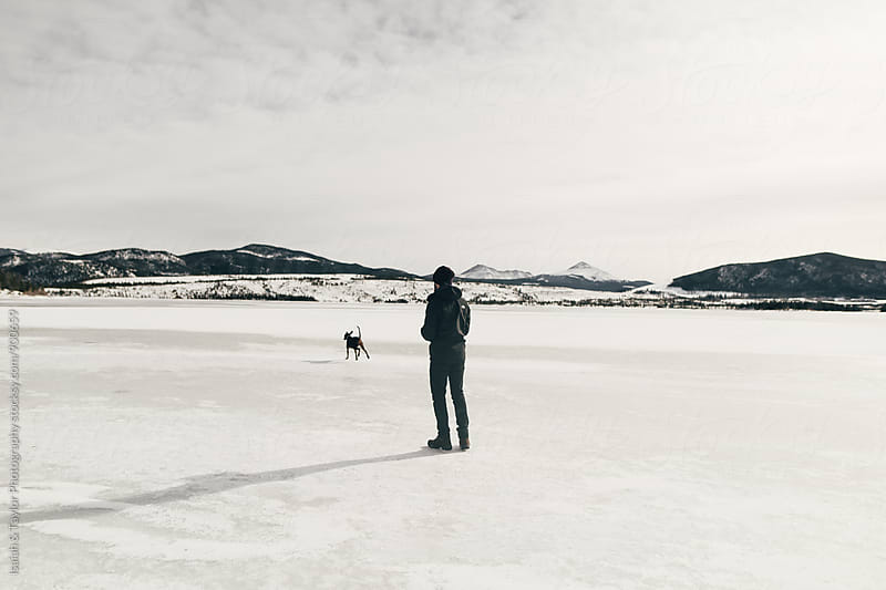 Man and his dog crossing frozen lake by Isaiah & Taylor Photography for Stocksy United