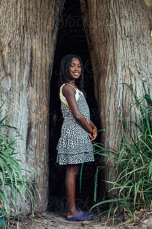 Pretty African American girl in a tree hollow by Gabriel (Gabi) Bucataru for Stocksy United