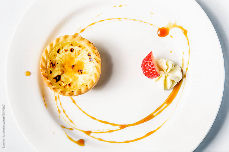 Tasty baked pudding tart on plate decorated with caramel sauce and slice of strawberry by Lawren Lu for Stocksy United