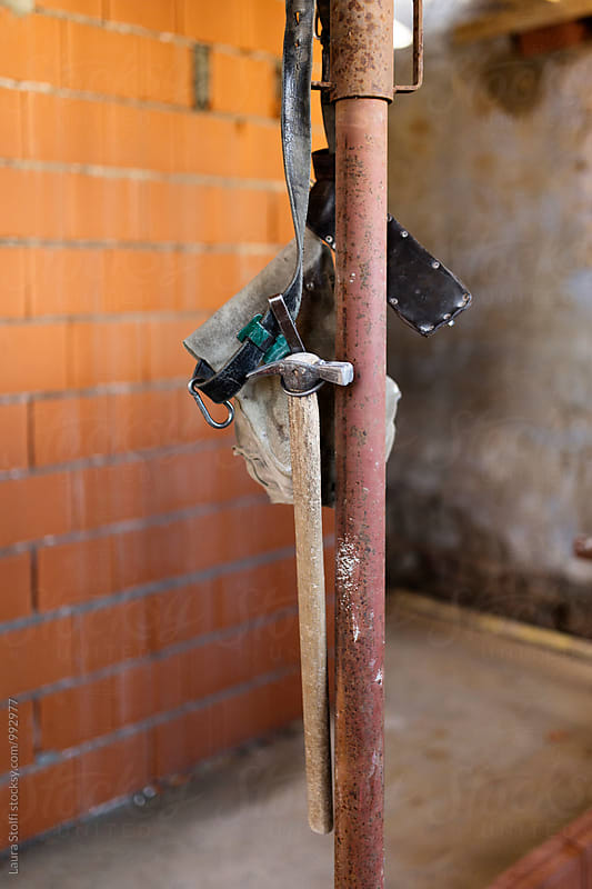 Carpenter's hammer and tools belt hung on building site by Laura Stolfi for Stocksy United
