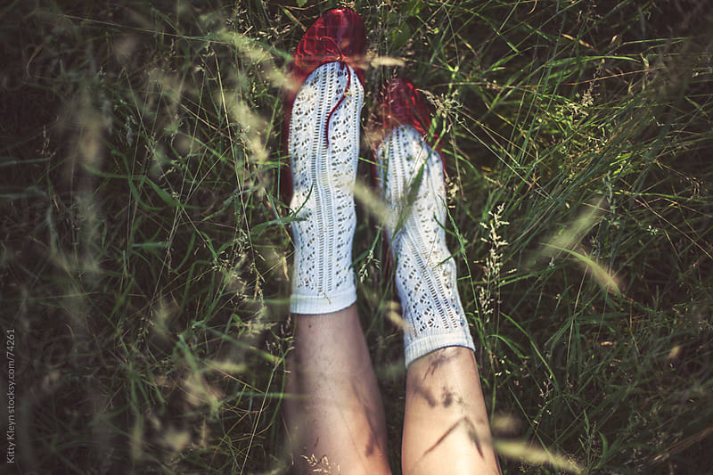 Little red shoes in the grass by Kitty Gallannaugh for Stocksy United