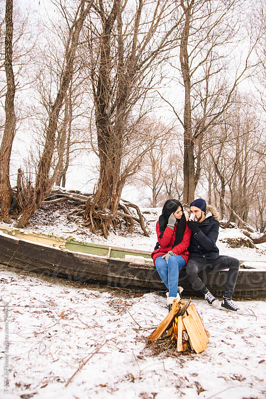 Couple sitting on the edge of boat, man drinking hot tea by T-REX & Flower for Stocksy United