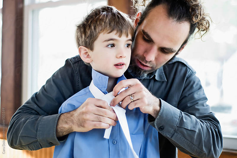 Father helps his son with his necktie by Cara Dolan for Stocksy United