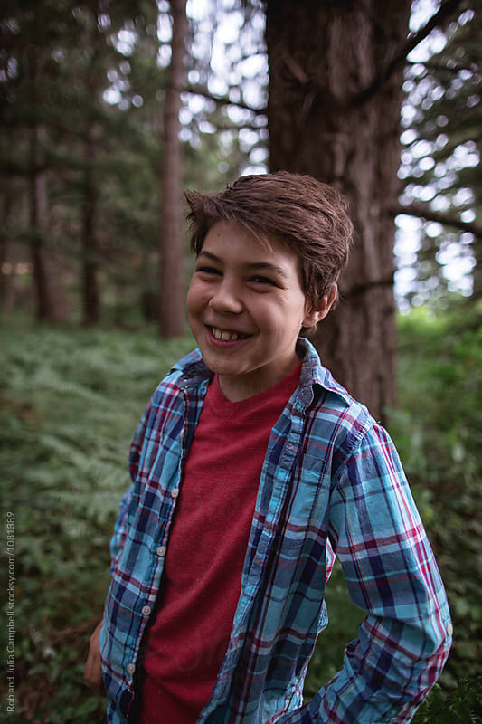 Young, happy preteen caucasian boy outside in nature by Rob and Julia Campbell for Stocksy United