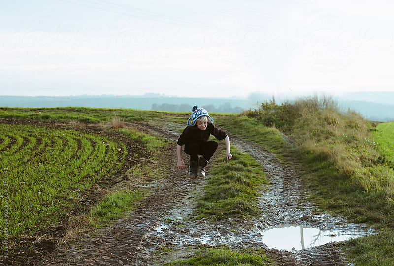 Boy jumping into muddy puddles by Helen Rushbrook for Stocksy United