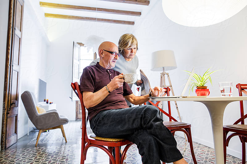 Elderly couple using laptop at home. by BONNINSTUDIO for Stocksy United