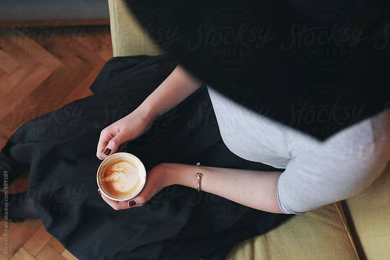 Young woman holding cup of coffee from above by Jovana Rikalo for Stocksy United