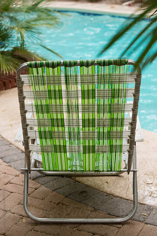 empty retro lawn chair sits beside pool by Tana Teel for Stocksy United