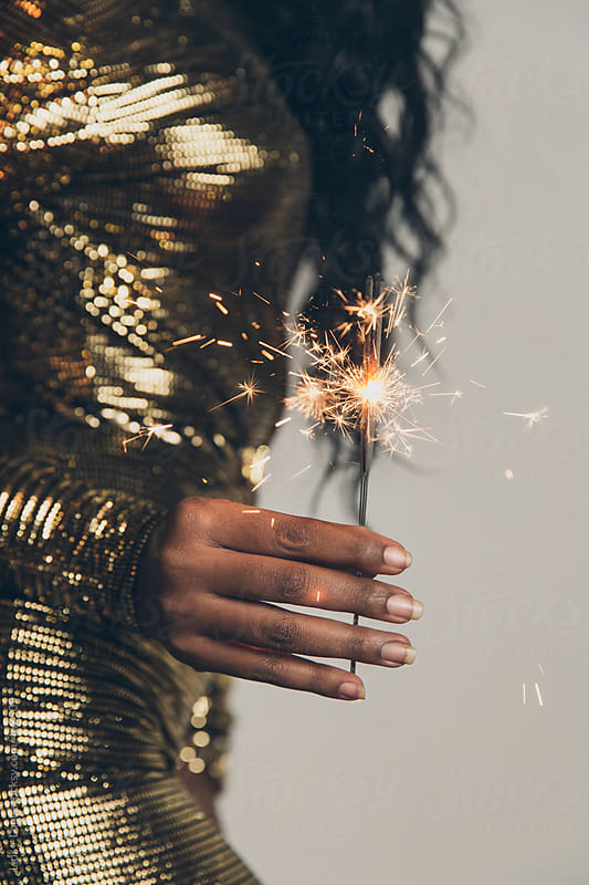 Hand of a black woman holding a sparkler by Lior + Lone for Stocksy United