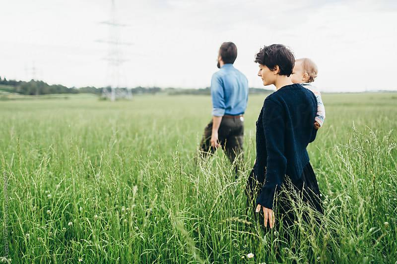 Beautiful family walking through the field  by Evgenij Yulkin for Stocksy United