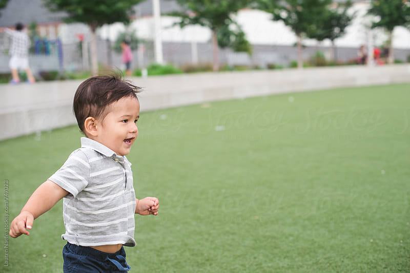 Toddler running and playing in the park by Lauren Naefe for Stocksy United
