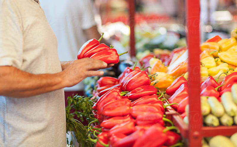 Man buying red bell peppers at the market. by Mosuno for Stocksy United