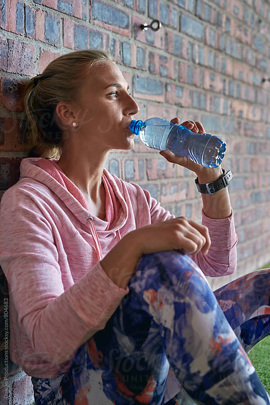 Fitness woman drinking water from bottle  by Daxiao Productions for Stocksy United