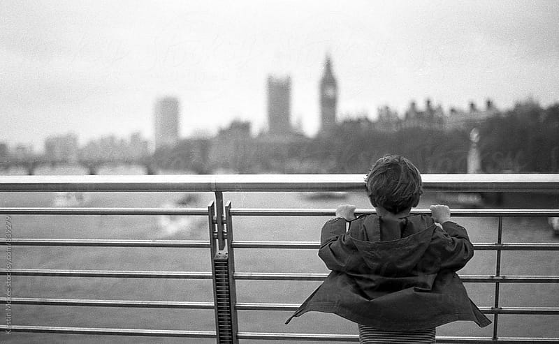 Boy standing on bridge looking at Big Ben by Kirstin Mckee for Stocksy United