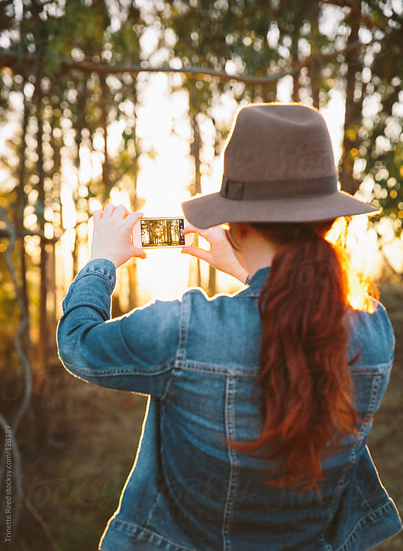Woman taking a photo in nature with her mobile phone by Trinette Reed for Stocksy United