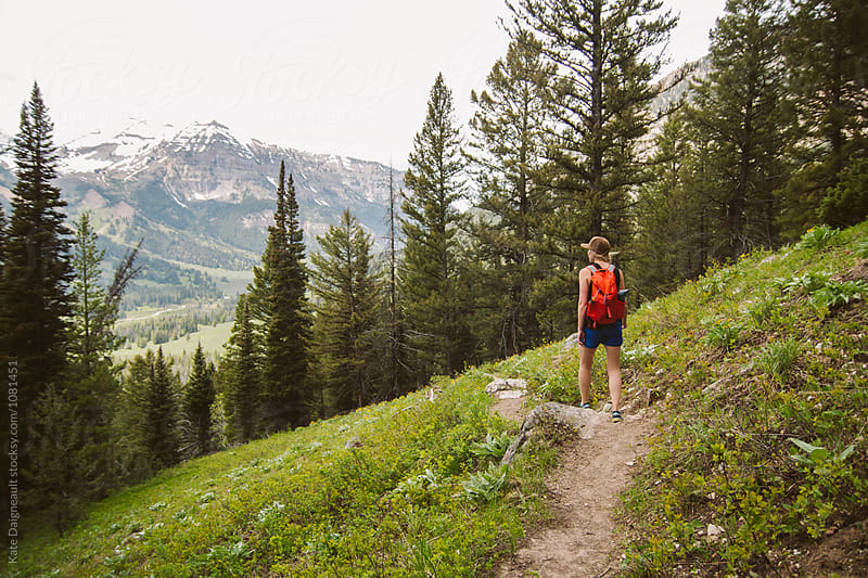 Young woman hiking a mountain trail. by Kate Daigneault for Stocksy United