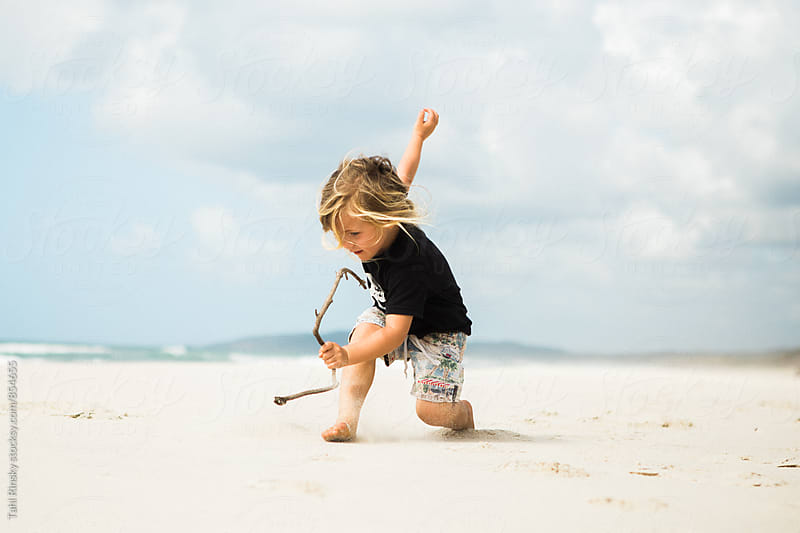 child running and playing with driftwood on an empty beach  by Tahl Rinsky for Stocksy United