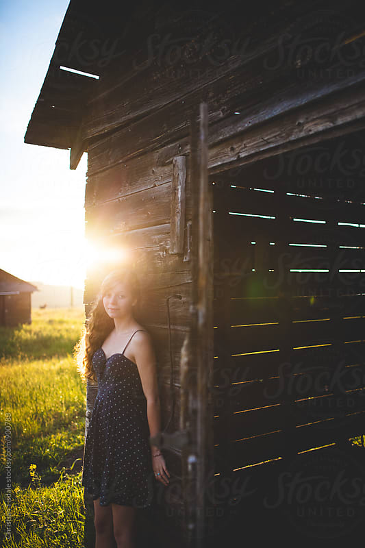 Vertical portrait of girl leaning on a barn at sunset with bright sunflare by Christian Tisdale for Stocksy United