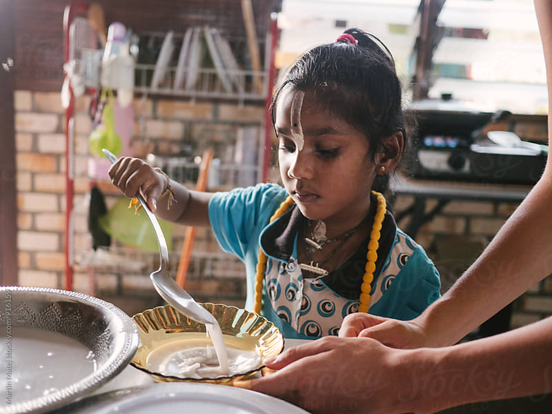 Young indian girl pouring milk into bowl by Martin Matej for Stocksy United