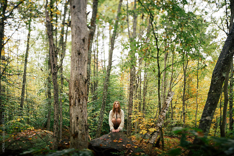 girl crouches in a New England forest  by HOWL for Stocksy United