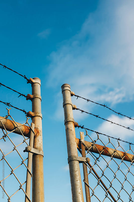 Detail of barbed wire and chain-link fence by Paul Edmondson for Stocksy United