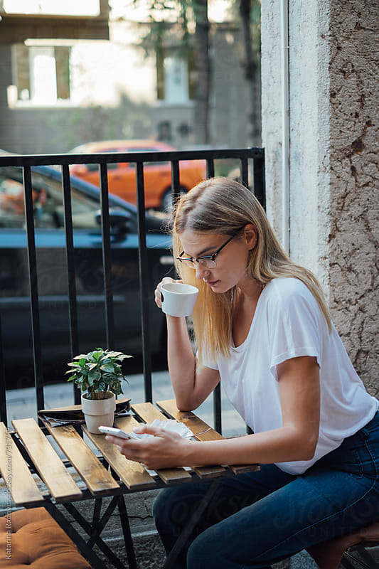 Blond Woman Sitting in a Cafe while Having Cofee by Katarina Radovic for Stocksy United