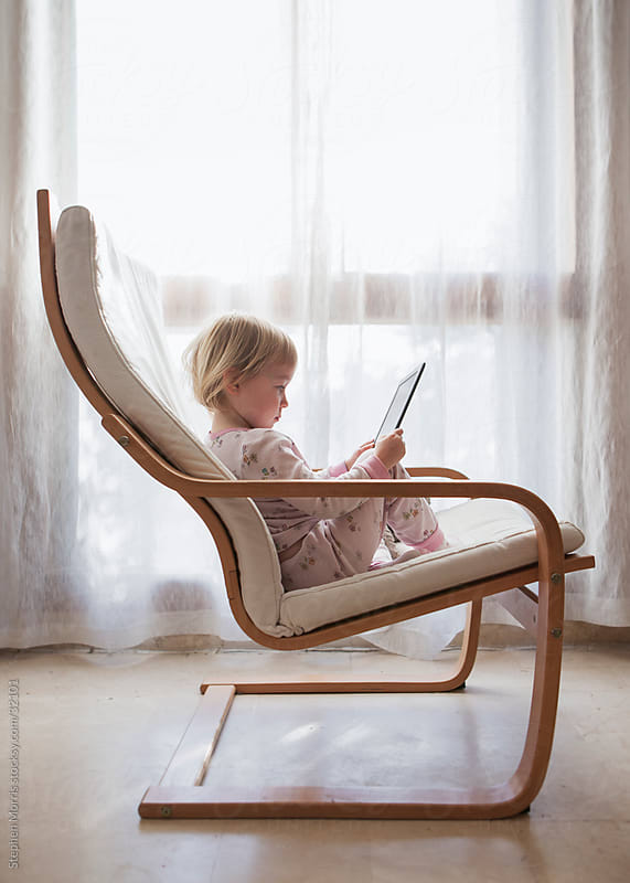 Little Girl Sitting Looking at Digital Tablet by Stephen Morris for Stocksy United