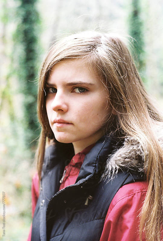 somber teenager in vest looking at camera by Tana Teel for Stocksy United