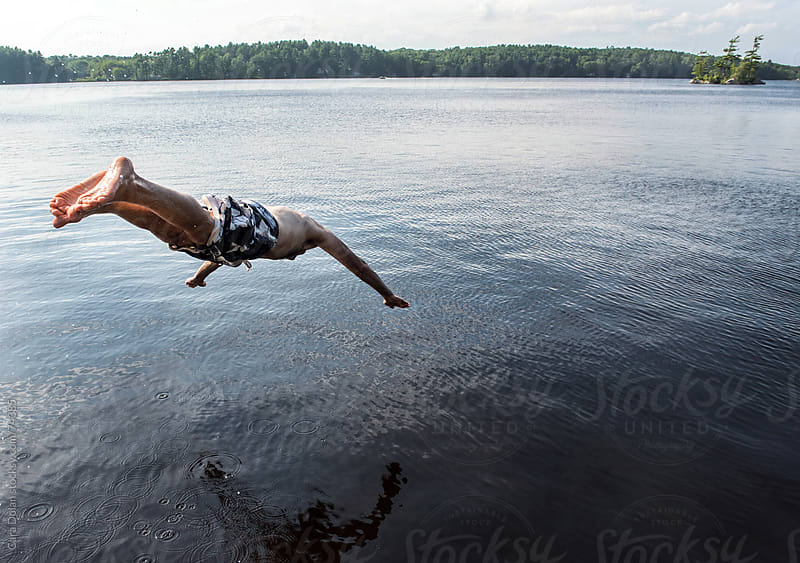 Man dives into a lake by Cara Slifka for Stocksy United