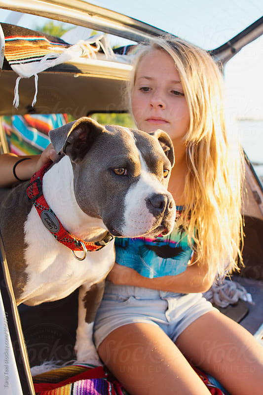 girl pets dog while sitting in back of hatchback by Tana Teel for Stocksy United