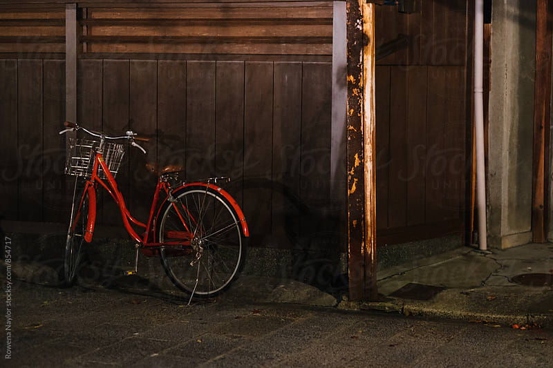 Vintage red bicycle at night in Japan by Rowena Naylor for Stocksy United