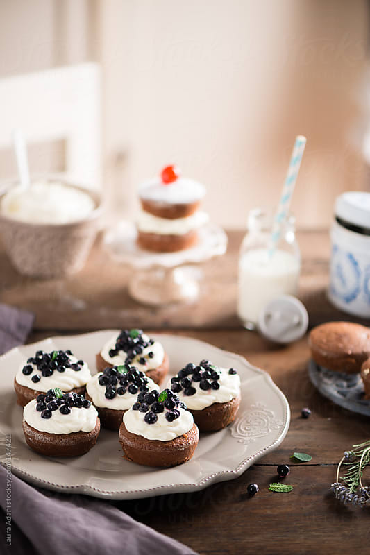 chocolate mini cake garnished with cream and blueberries by Laura Adani for Stocksy United