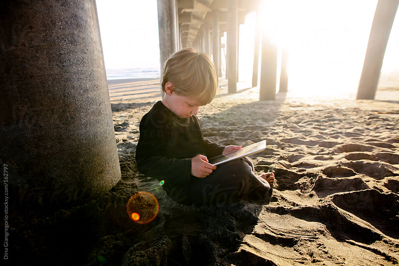 Toddler boy playing on tablet at the beach by Dina Giangregorio for Stocksy United