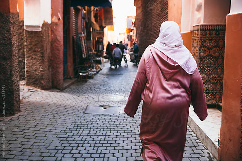 Woman walking along the street in Morocco by Alejandro Moreno de Carlos for Stocksy United