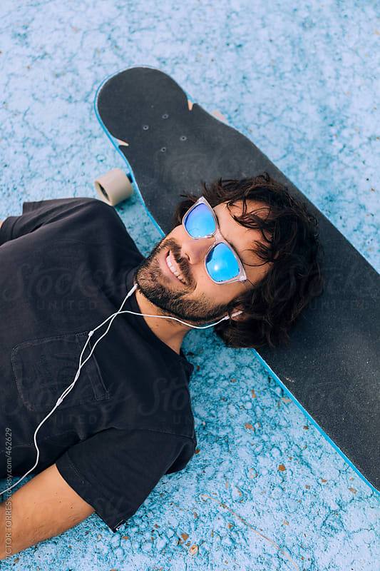 Young Hipster Man with Headphones Sitting on a Longboard by VICTOR TORRES for Stocksy United