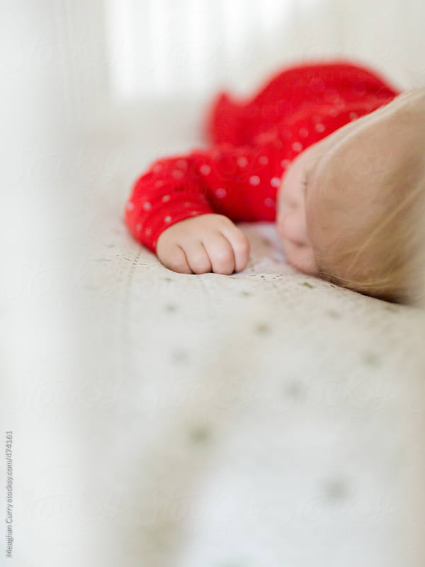 baby asleep in her crib wearing Christmas pajamas by Meaghan Curry for Stocksy United