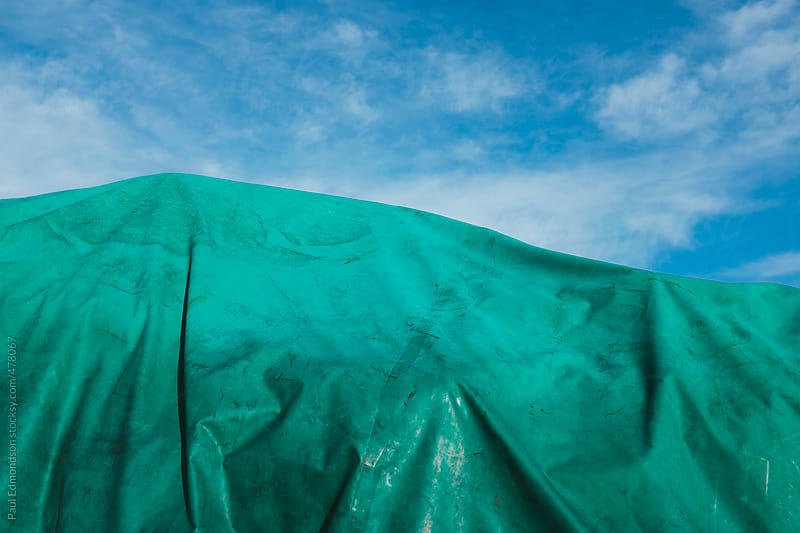 Plastic green tarpaulin covering pile of commercial fishing equipment by Paul Edmondson for Stocksy United
