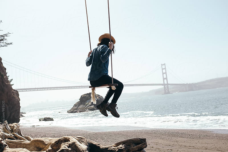 Swinging on a tree swing on a beach by the Golden Gate Bridge. by Lucas Saugen for Stocksy United