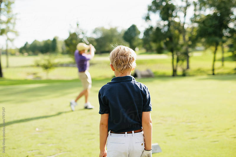 young golfer watches his father on the course  by Kelly Knox for Stocksy United