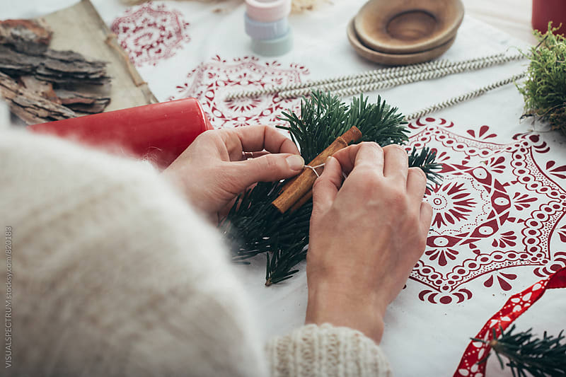 DIY Christmas - Close Up of Female Hands Tying Cinnamon Sticks to Fir Twigs by Julien L. Balmer for Stocksy United