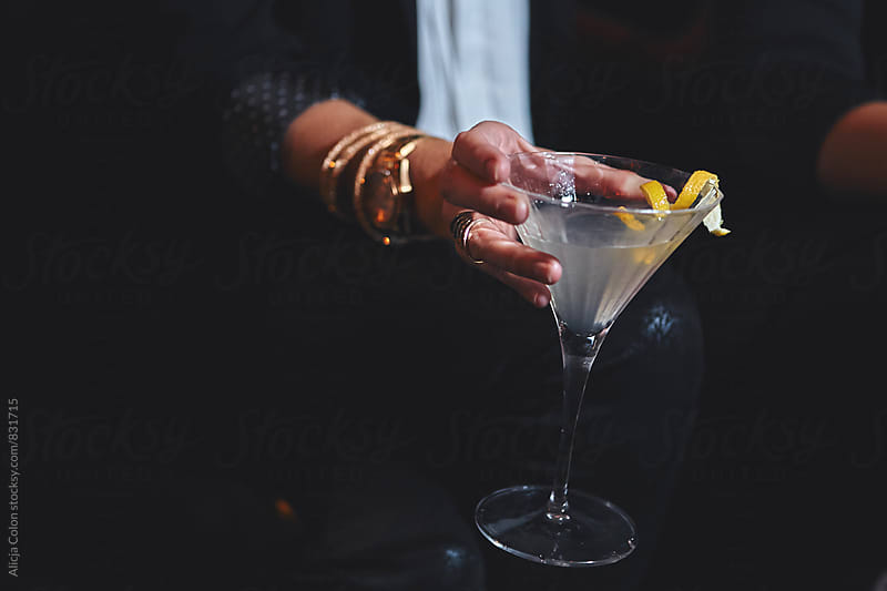 Holding a lemon martini in a lounge by Alicja Colon for Stocksy United