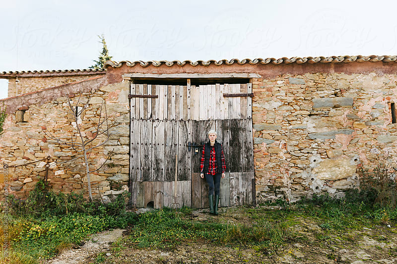 Portrait of a blonde woman standing in front of a rural house. by BONNINSTUDIO for Stocksy United