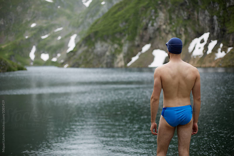 Young man swimmer getting ready for training in a lake by Miquel Llonch for Stocksy United