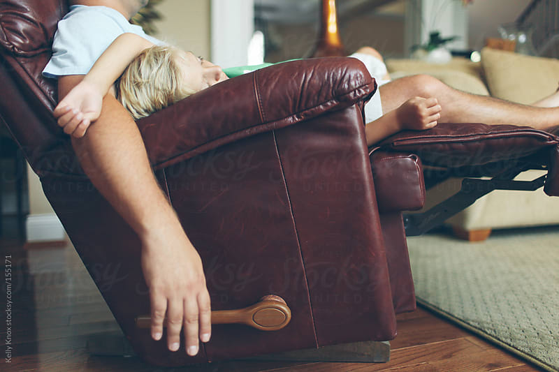 father and son asleep in a recliner by Kelly Knox for Stocksy United