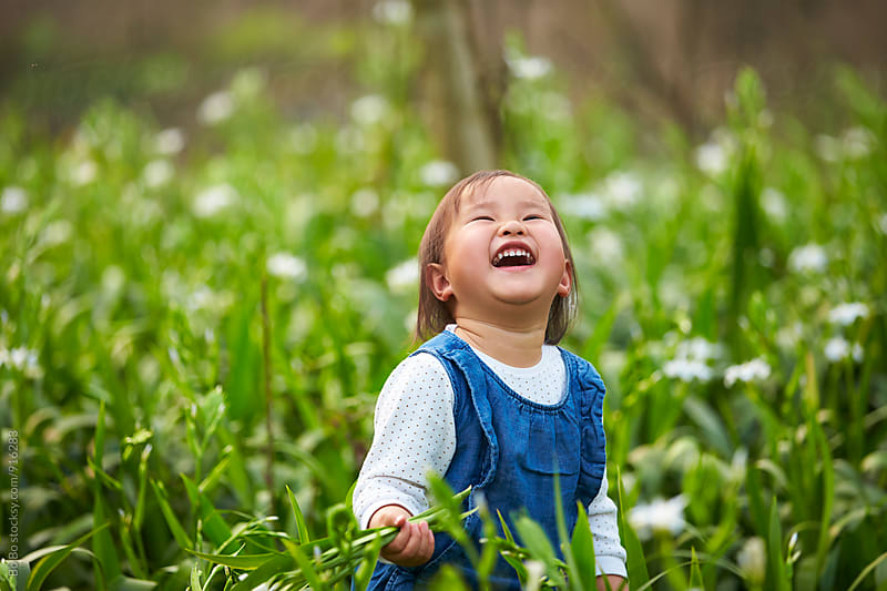 happy little asian girl in spring field by Bo Bo for Stocksy United