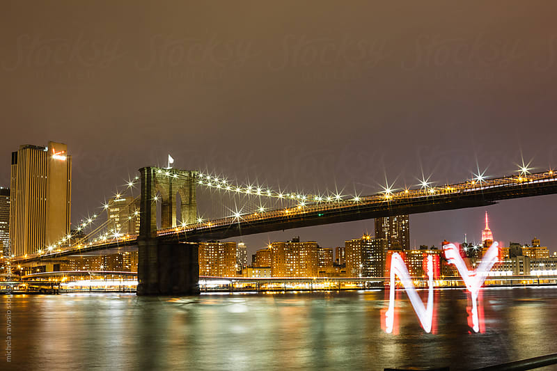 NY written illuminated, with the Brooklyn Bridge in the background, New York City by michela ravasio for Stocksy United