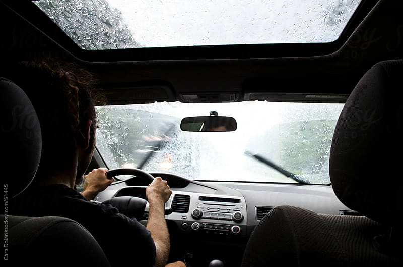 Man driving his car in the rain by Cara Slifka for Stocksy United